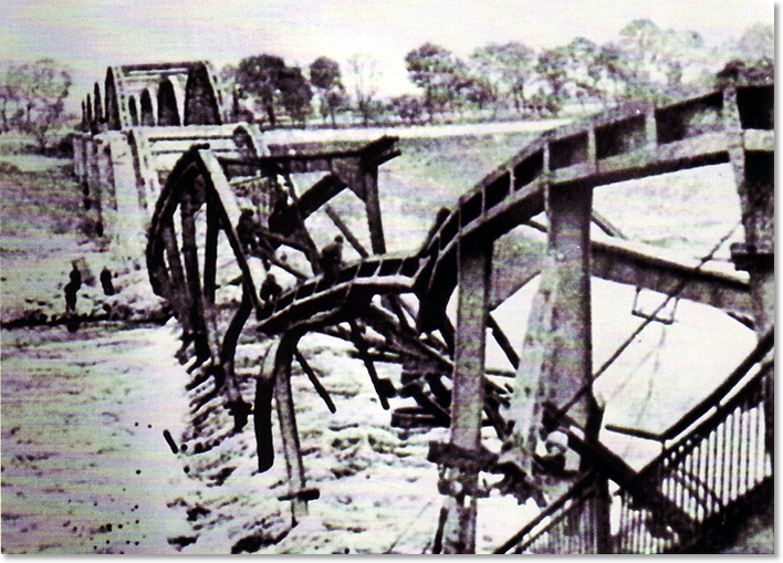 Figure 7. Robertson Patrol 1600 (4:00 PM). The scene at the damaged bridge over the Elbe in Torgau about 1600, April 25, 1945. Americans 2nd Lieutenant William D. Robertson and Pfc Frank Huff, Hq 1st Bn 273rd Inf Rgt climbing the steel skeleton of the blasted bridge over the Elbe River in Torgau to meet Soviet Lieutenant Alexander Silvashko and Sergeant Nikolai Andrejew, 58th Guards Division.
