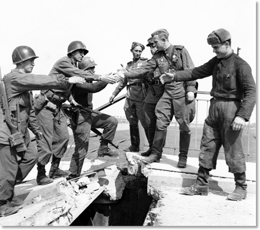"Figure 1: This staged photo is arguably the most famous of the many handshake photos taken between American and Soviet soldiers that were taken to commemorate the historic Link-Up. According to historian Dr. Uwe Niedersen, author of ""Elbe Link-Up"" (2005: Demand Society Encounters Europe e.V.). International News war correspondent Allan Jackson quickly arranged this photo on April 26, 1945 at about 12:00. The soldiers that Jackson were sightseeing and trading Vodka and chocolate. The American 69th soldiers pictured (left) were attached to Colonel Charles M. Adams, 273rd Inf Rgt Commander, and were in Torgau preparing for the formal meeting between the American 69th's General Reinhardt and the Soviet 58th's General Russakov. According Dr. Niedersen Col. Adams' report identifies ""Kirzenbaum"" as ""the American in the middle of the photo."" The Soviet soldier in the center of the photo is Lt. Charles Thaw, a Pole drafted into the Soviet Army in 1940. Source: Joe Lipsius, Regtl Hq & Cn Co 272nd Inf Reg."
